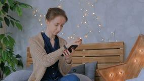 De vrouw synchroniseert wearable gegevens van de geschiktheidsdrijver met smartphone app stock videobeelden