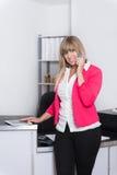 De vrouw telefoneert in het bureau Stock Foto
