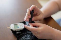 De vrouw test haar bloedsuiker gebruikend glucosemeter stock afbeelding