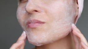 De vrouw is toepast een het schuimen middel om de huid te reinigen Close-up van een vrouwen` s gezicht Zeepbels op de huid Het co stock videobeelden
