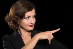 De vrouw toont een vinger aan de kant Royalty-vrije Stock Afbeelding