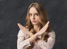 De vrouw toont het teken van het eindeonderscheid met gekruiste handen royalty-vrije stock foto's