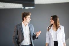 De vrouw toont iets abstract aan haar partner Exemplaarruimte tussen twee bedrijfspersonen gekleed na strikte kleding-kabeljauw Stock Fotografie