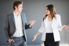 De vrouw toont iets abstract aan haar partner Exemplaarruimte tussen twee bedrijfspersonen gekleed na strikte kleding-kabeljauw Royalty-vrije Stock Foto's