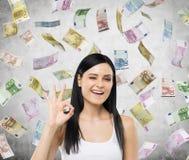 De vrouw toont o De euro nota's vallen onderaan over concrete achtergrond Royalty-vrije Stock Afbeeldingen