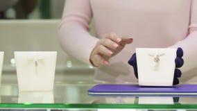 De vrouw toont verschillende juwelengoederen bij de winkel stock footage
