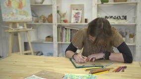 De vrouw trekt beeld of kaartzitting bij bureau met kleurrijke potloden stock footage
