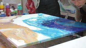 De vrouw trekt een beeld van een vloeibare kunst op canvas stock video