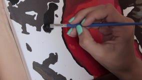 De vrouw trekt een borstel op canvas stock videobeelden