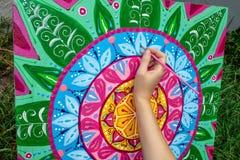 De vrouw trekt een mandala, hand met een borstelclose-up vector illustratie
