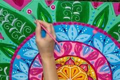 De vrouw trekt een mandala, hand met een borstelclose-up royalty-vrije illustratie