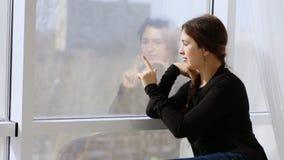 De vrouw trekt in het venster de hartvinger en romantische sighs stock videobeelden