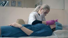 De vrouw trekt wenkbrauwen van cliënt met hulpmiddel in kliniek uit stock videobeelden