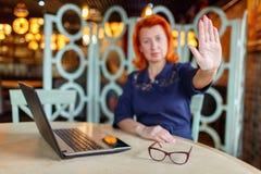 De vrouw uit nadruk toont eindeteken bij lijst in koffie royalty-vrije stock foto's