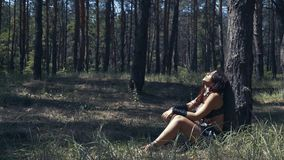 De vrouw van Amazonië in leerkleren rust onder een boom in het bos stock video