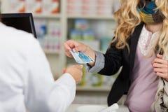 De Vrouw van apothekerreceiving money from voor Geneesmiddelen Stock Afbeelding