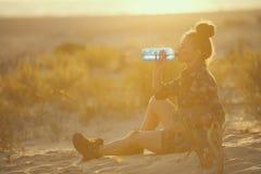 De vrouw van de avonturenreiziger op zeekust bij zonsondergang drinkwater royalty-vrije stock afbeelding