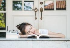 De vrouw van de close-upslaap nadat zij voor lezing op marmeren lijst voor huis vermoeide stock afbeeldingen