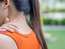 De vrouw van de close-upsport voelt pijn op haar hals en schouder stock fotografie