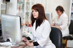 De vrouw van de apotheekchemicus in drogisterij Stock Afbeeldingen