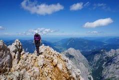 De vrouw van de bergbeklimmer bovenop een berg royalty-vrije stock afbeelding