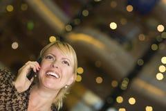 De Vrouw van de blonde op Haar Telefoon van de Cel in de Lichten van de Stad Royalty-vrije Stock Afbeeldingen