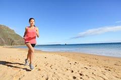 De vrouw van de de atletenagent van joggingsporten op strand stock afbeeldingen