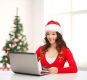 De vrouw van de kerstmanhelper met laptop en creditcard Royalty-vrije Stock Fotografie