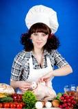 De vrouw van de kok houdt een Ruwe Kip stock afbeeldingen