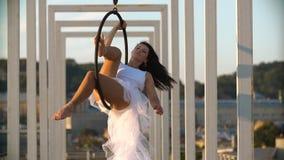 De vrouw van de luchtgymnastiek voert acrobatiektrucs op luchthoepel uit stock videobeelden