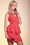 De vrouw van de make-upkunstenaar in de rode borstels van de kledingsholding stock fotografie