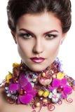 De vrouw van de manierschoonheid met bloemen in haar haar en rond haar hals Perfecte Creatief maakt omhoog en Haarstijl Stock Foto