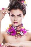 De vrouw van de manierschoonheid met bloemen in haar haar en rond haar hals Perfecte Creatief maakt omhoog en Haarstijl Royalty-vrije Stock Afbeeldingen
