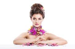 De vrouw van de manierschoonheid met bloemen in haar haar en rond haar hals Perfecte Creatief maakt omhoog en Haarstijl Royalty-vrije Stock Fotografie