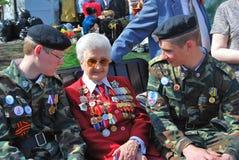 De vrouw van de oorlogsveteraan en de tqo jonge mannen zitten op een bank Stock Foto