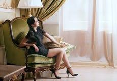 De vrouw van de retro-stijl in leunstoel Stock Afbeelding