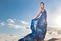 De vrouw van de schoonheid in blauwe kleding op de woestijn Stock Afbeeldingen
