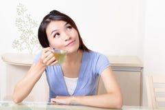 De vrouw van de schoonheid ontspant drinkt thee met huisachtergrond Royalty-vrije Stock Afbeeldingen