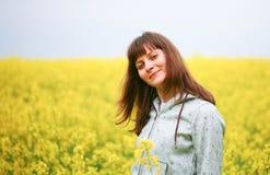 De vrouw van de schoonheid op bloemgebied Stock Afbeelding