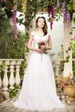 De vrouw van de schoonheid in witte kleding Bruid, huwelijk in tuin Brunette Stock Foto