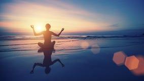 De vrouw van de silhouetmeditatie op de achtergrond van het overzees en de zonsondergang Royalty-vrije Stock Foto's