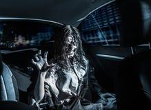 De vrouw van de verschrikkingszombie met bloedig gezicht in de auto stock foto's