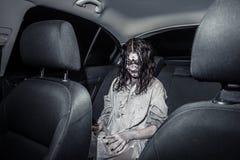 De vrouw van de verschrikkingszombie met bloedig gezicht in de auto stock foto