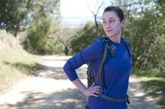 De vrouw van de wandelaar in blauw lang kokeroverhemd kijkt weg aan linkerzijde Royalty-vrije Stock Foto