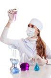De vrouw van de wetenschapper in laboratorium met chemisch glaswerk Stock Foto's