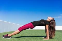 De vrouw van de yogageschiktheid het planking in stijgende plank stelt stock foto