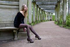 De vrouw van de zitting in de oude tuin Stock Foto's