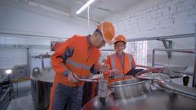 De vrouw van fabrieksingenieurs met mannetje in helmen met tabletlaptop controleert productie-installatie terwijl het bespreken v stock footage