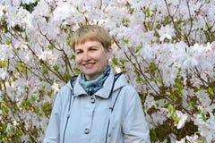 De vrouw van gemiddelde jaren tegen de achtergrond van de tot bloei komende rododendron van Shlippenbakh royalty-vrije stock afbeeldingen