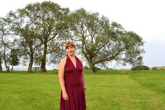 De vrouw van gemiddelde jaren tegen de achtergrond van bomen Stock Afbeelding